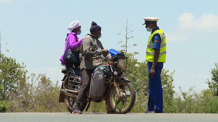 A police officer questions a boda boda rider and his pillion at the Thika roadblock near Blue Post Hotel on Monday