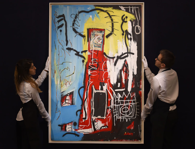 Sotheby's employees adjust Untitled (One Eyed Man or Xerox Face) painted in 1982 by Jean-Michel Basquiat. The work sold for $110.5m on May 18 2017. Picture: GETTY IMAGES
