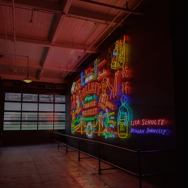 Darkly lit room with a wall full of neon lights