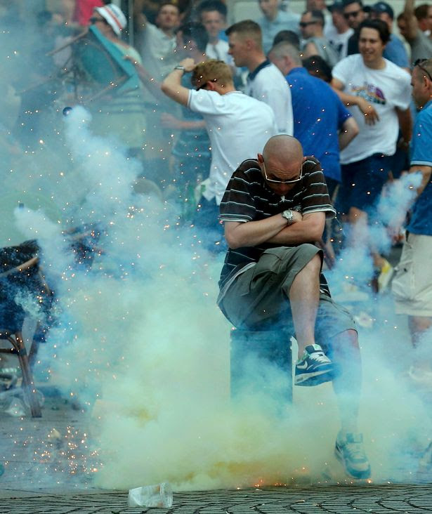 A teargas grenade explodes near an England fan ahead of England's EURO 2016 match in Marseille, France