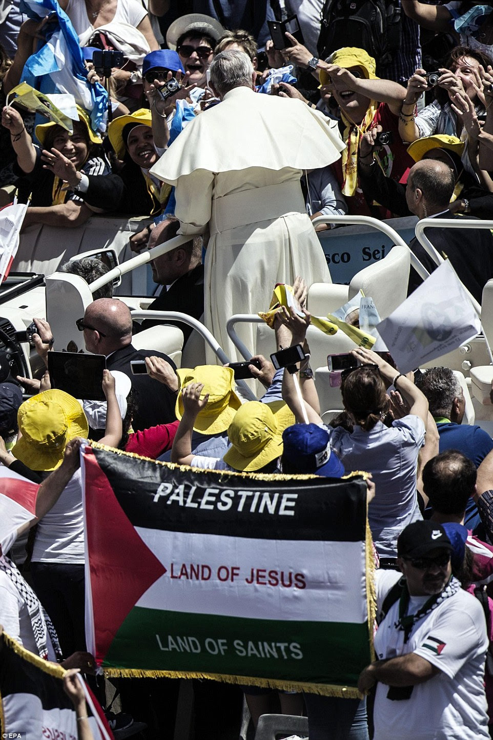 The Pope greets the cheering crowds at the end of the service, many of whom were waving Palestinian flags bearing the message 'Palestine: Land of Jesus, Land of Saints'