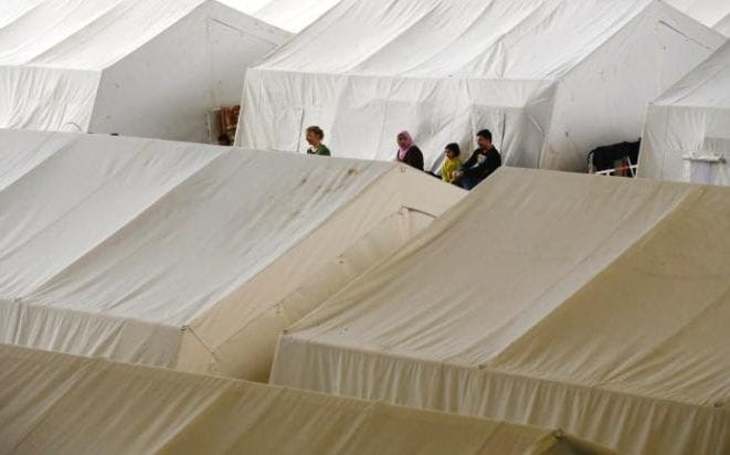 A file photo of people gathering among tents at a shelter for migrants inside a hangar of the former Tempelhof airport in Berlin