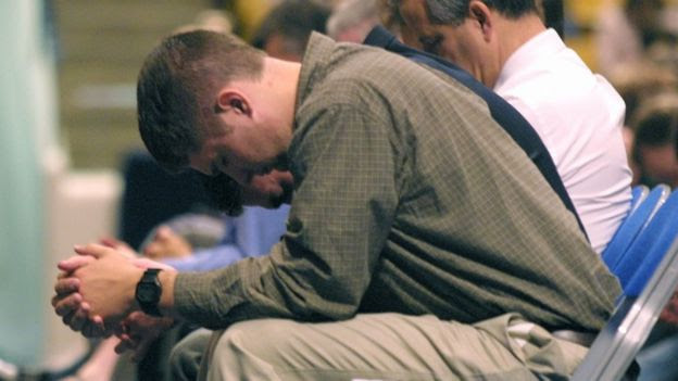 A student bows his head in prayer at Brigham Young university