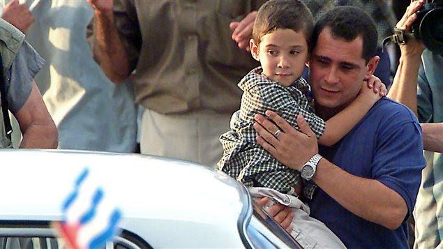 Elian Gonzalez dans les bras de son père à leur arrivée à l'aéroport Jose Marti le 29 juin 2000 à La Havane.