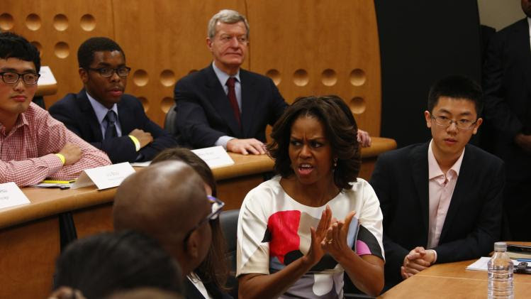 Michelle Obama claps as she and U.S. ambassador Baucus sit among students during virtual discussion with American youth through the Internet at the Peking University in Beijing