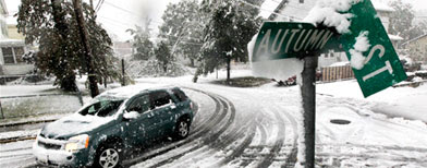 A vehicle makes its way at the snow-covered intersection of Autumn and Grove Streets in Lodi, N.J., following a rare October snowstorm that hit the region, Saturday, Oct. 29, 2011. (AP Photo/Julio Cortez)