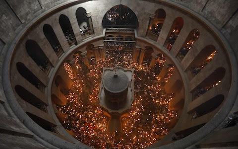 "Christian Orthodox worshippers hold up candles during the ceremony of the ""Holy Fire"" as thousands gather in the Church of the Holy Sepulchre in Jerusalem's Old City, on April 15, 2017, during Orthodox Easter ceremonies"
