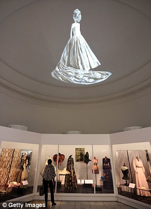 An image of a dress is projected on to the ceiling at the Ballgowns: British Glamour Since 1950 exhibition