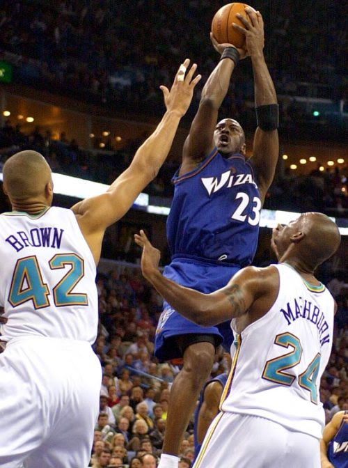 Michael Jordan hits a fallaway jump shot to pass Wilt Chamberlain for third on the NBA's all-time scoring as the Washington Wizards played the New Orleans Hornets on Jan. 22, 2003. The basket, which gave Jordan 14 points with a minute left in first half, put Jordan's career scoring at 31,420 points in his 1,032nd regular season game. (Andrew J. Cohoon/AP)