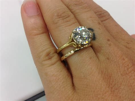 OEC solitaire with side scrolls in yellow gold by David