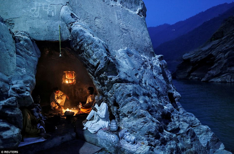 Hindu priests sit inside a cave as they perform evening prayers on the banks of the river Ganges in Devprayag, India, on March 28. The town is a pilgrimage hotspot for followers of the religion