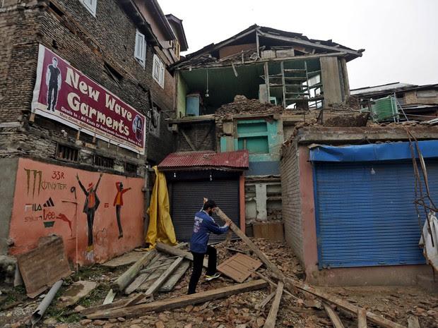 Homem retira destroços após casa desabar parcialmente após terremoto atingir Srinagar, na Índia, no domingo (10) (Foto: Danish Ismail/Reuters )