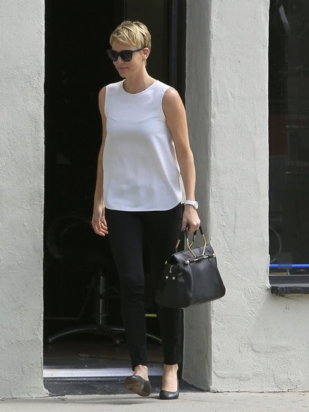 'Mad Max: Fury Road' actress Charlize Theron grins with glee after a visit to the nail salon in West Hollywood, California on May 17, 2013. Theron looked gorgeous in a simple sleeveless white top and black pants and showed off her cute new look as her hair grows out after she shaved it for her 'Mad Max' role.
