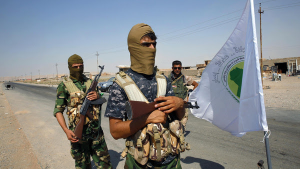 File photo of fighters from the Shi'ite Badr Brigade militia standing near their flag as they guard at a checkpoint outside the town of Sulaiman Pek