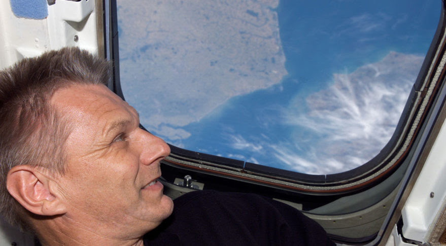 Piers Sellers, climate scientist and NASA astronaut, looks out the window of Space Shuttle Discovery during a 2006 mission. He was honored posthumously at the 33rd Space Symposium Wednesday. Credit: NASA