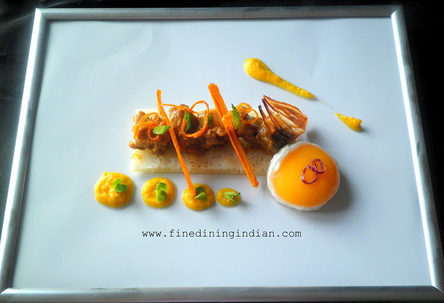 slow braised lamb shoulder in spiced gravy appam fried egg carrot and cumin puree,crisps of carrot and onion on picture frame