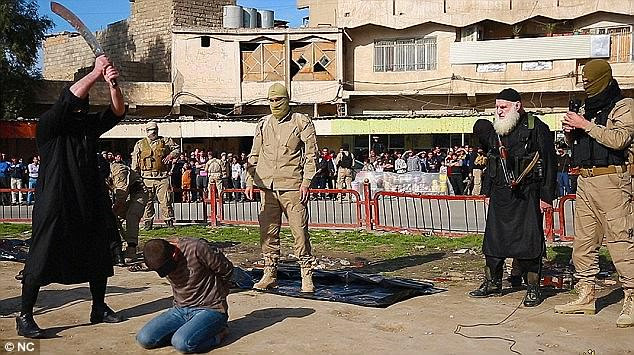 On what appears to be a roundabout, members of the public gather the other side of the road as an ISIS executioner brings down the huge blade