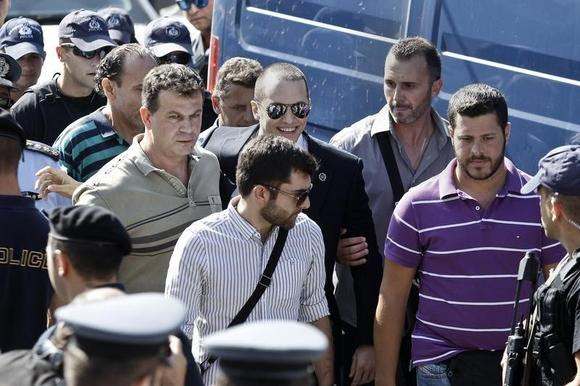 Far-right Golden Dawn lawmaker Ilias Kasidiaris (C), who is in custody pending trial, arrives escorted by plainclothes police for the Athens council swearing-in ceremony August 29, 2014. REUTERS/Alkis Konstantinidis