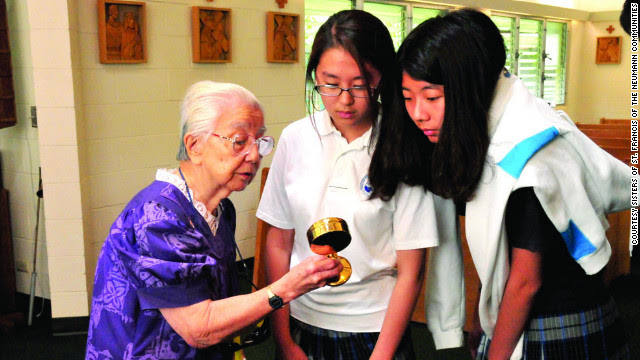 Sister Agnes Hino shows a Mother Marianne Cope relic to Ho Kyong Kim and Bo Kyong Hong, seventh-graders at St. Francis School in Honolulu.