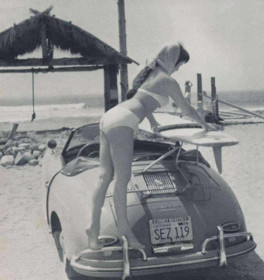 Woman removing a surf board from a Porsche Speedster