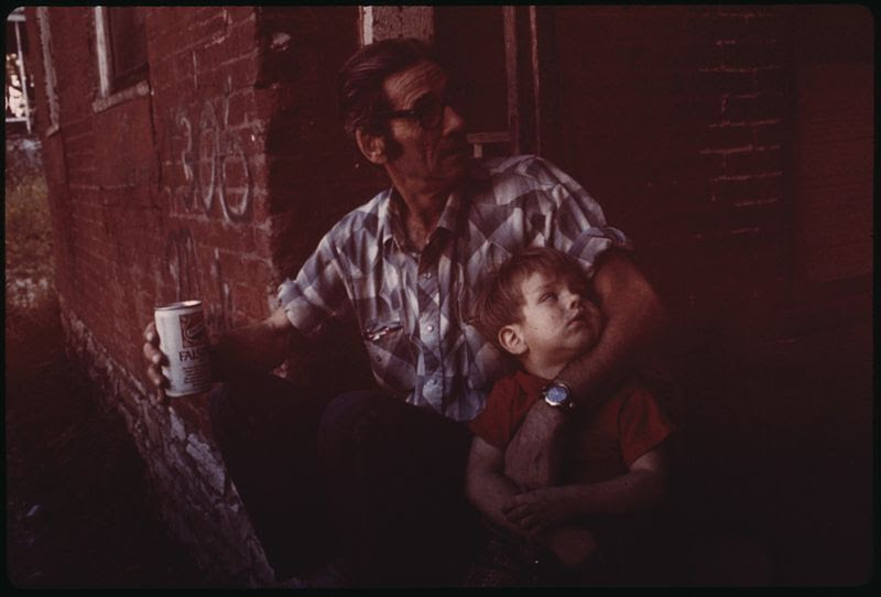 File:ERNEST WATKINS OF MULKY SQUARE, BISCUIT COMPANY WORKER AND FATHER OF NINE, SITS ON HIS FRONT DOORSTEP WITH HIS... - NARA - 553520.jpg