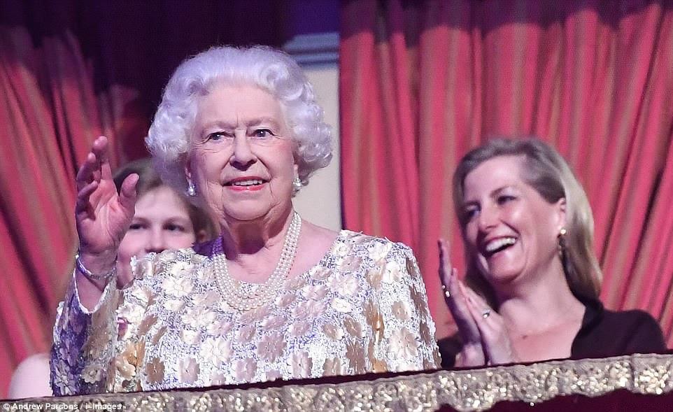 A rainha acena e sorri da caixa real enquanto assiste a seu concerto de aniversário no Royal Albert Hall