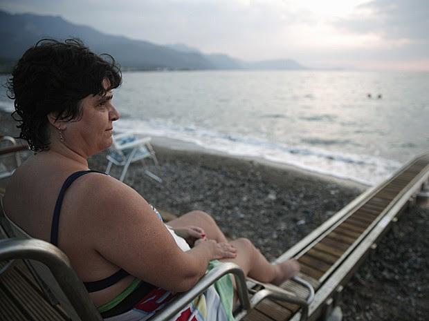Matoula Kastrioti, de 46 anos, que sofre de esclerose múltipla, observa praia em Alepochori (Foto: Yorgos Karahalis/Reuters)