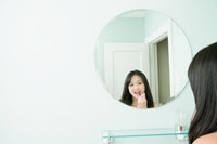 Photo of girl looking in mirror. How important is outward appearance really?