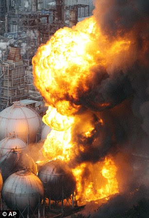 Giant fireballs rise from a burning oil refinery in Ichihara, Chiba Prefecture (state) after Japan was struck by a strong earthquake off its northeastern coast Friday, March 11, 2011.