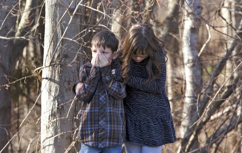 Crianças se amparam após tiroteio na escola Sandy Hook em Newtown, Connecticut