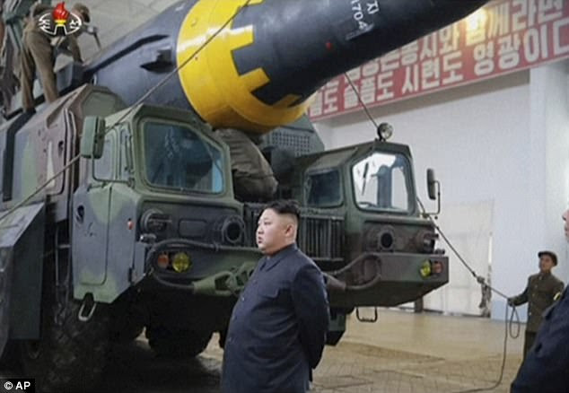 Kim Jong-Un, North Korea's leader, stands underneath a huge missile which was said to have been launched on Sunday