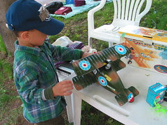 Little boy looking at toy biplane