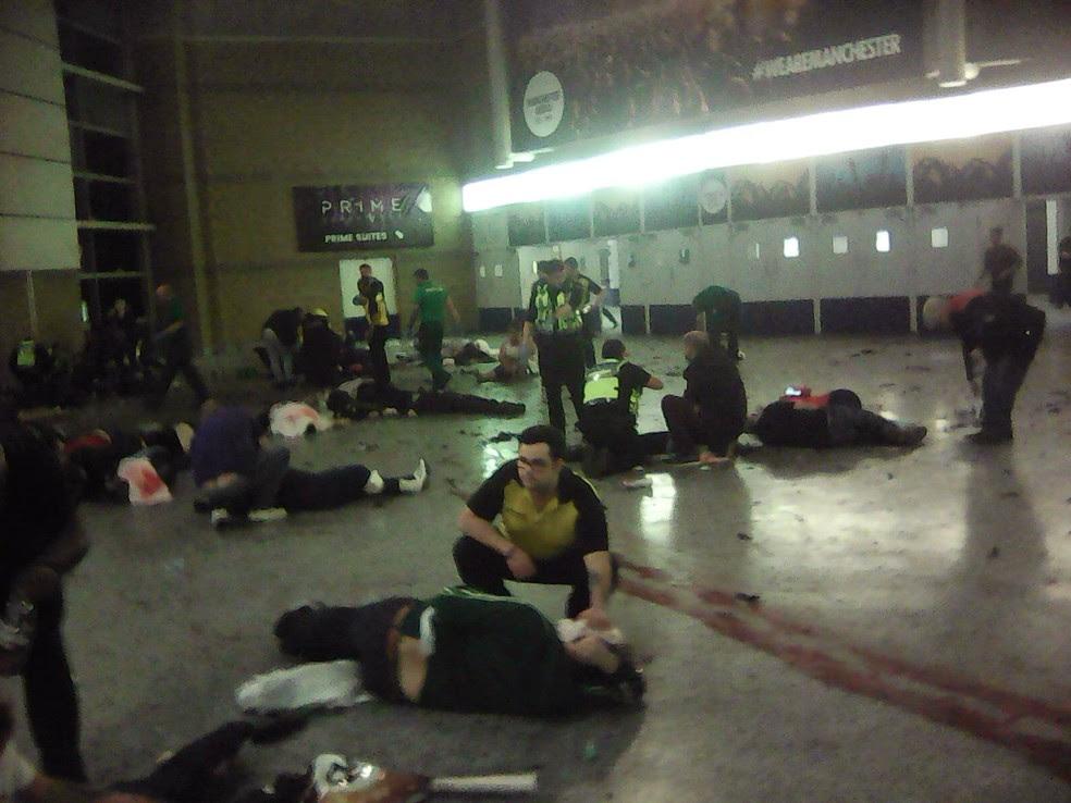 Policiais e outras pessoas tentam socorrer feridos após explosão na Manchester Arena durante show da cantora Ariana Grande na noite de segunda-feira (22) (Foto: PA via AP)