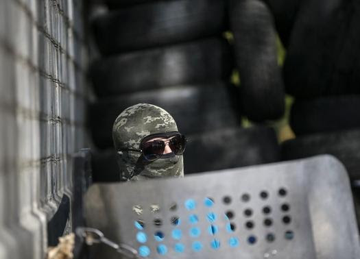 A pro-Russian armed man stands guard at the police headquarters in the eastern Ukrainian town of Slaviansk April 25, 2014. REUTERS-Gleb Garanich