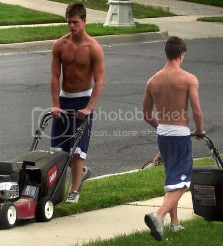two shirtless young man wearing baggy shorts are mowing a lawn a suburban street