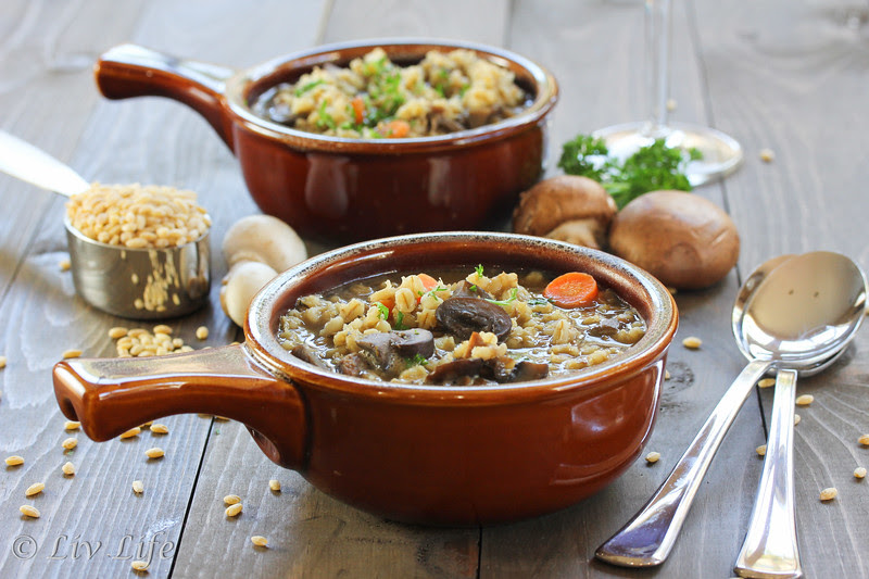 Beef and Barley Soup with Mushrooms in brown bowl on wood table