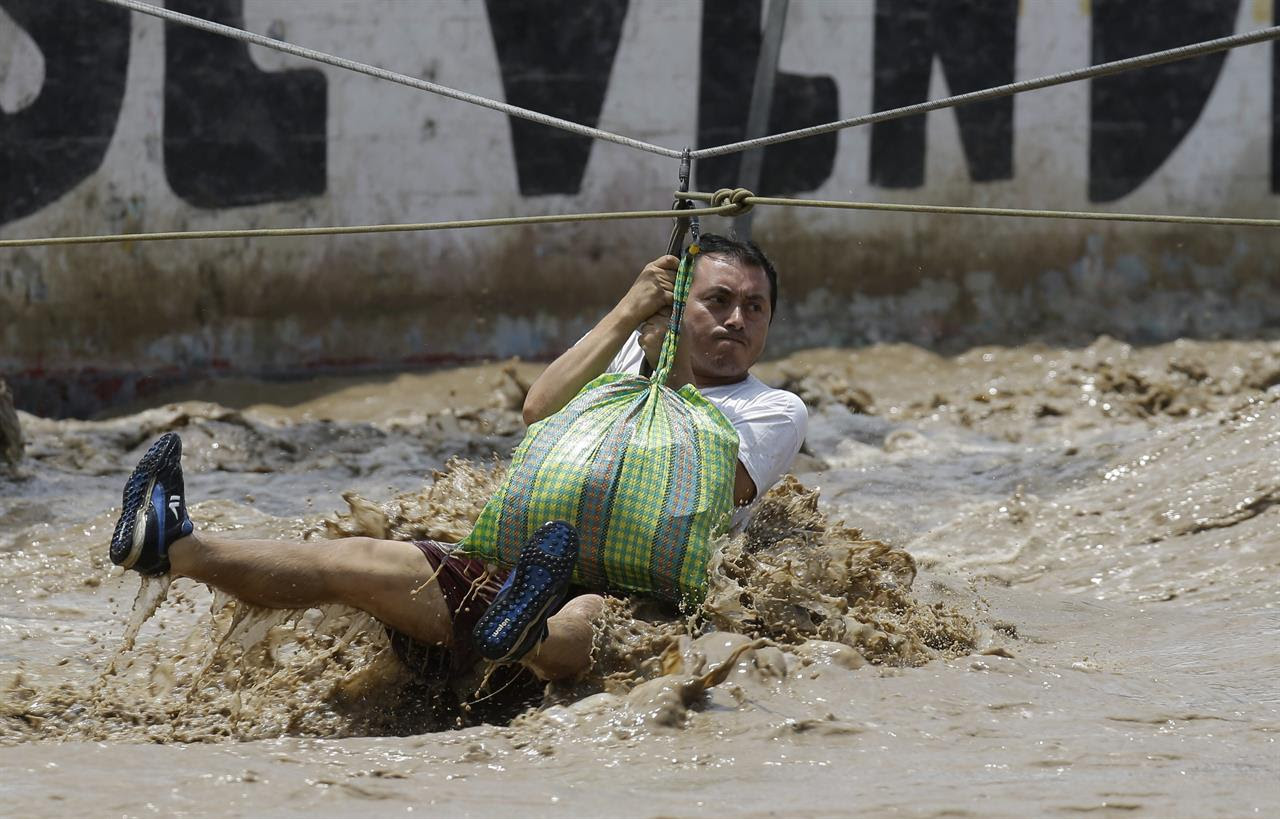 A man is pulled to safety in a zipline harness in Lima, Peru, Friday, March 17, 2017. The number of people killed in Peru following intense rains and mudslides wreaking havoc around the Andean nation climbed to 67 Friday, with thousands more displaced from destroyed homes and others waiting on rooftops for rescue.