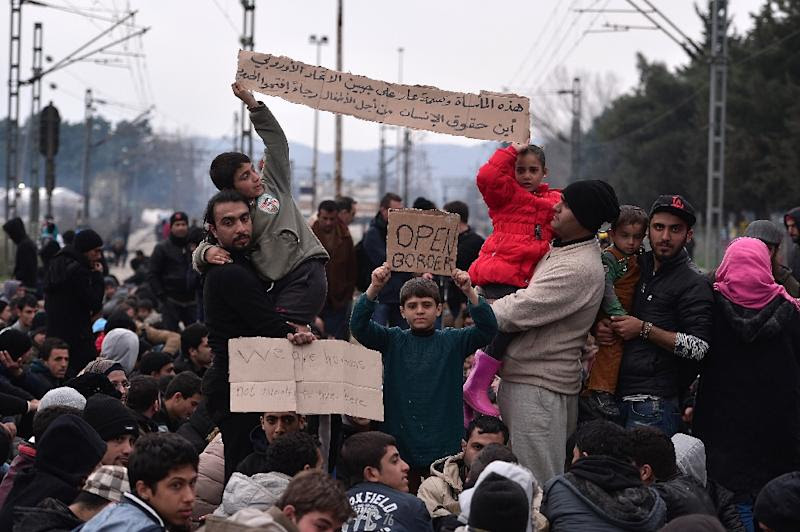 "Syrian and Iraqi refugees trapped at the  Greek-Macedonian border demonstrate, shouting ""open the border"" as they block the train tracks on February 28, 2016"