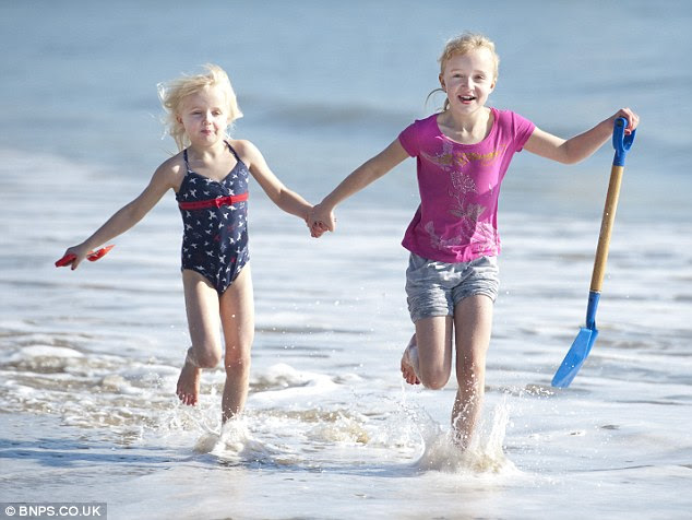Sun: Two young girls run along the beach at Bournemouth today as the cloud stays away