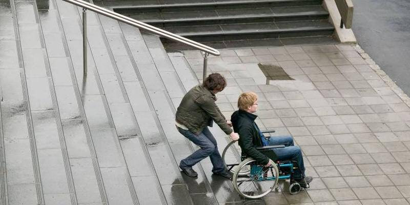 Man-helping-disabled-person