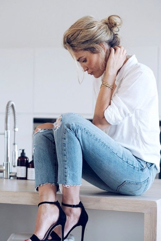 Le Fashion Blog Effortless Look Camilla Pihl Low Messy Bun White Button Down Shirt Stack Of Gold Bracelets Ripped Raw Hem Skinny Jeans Black Ankle Strap Heeled Sandals Via Camille Pihl