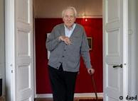 Tranströmer standing in a doorway surrounded by books