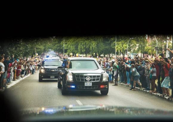 Cubanos saludan al Presidente Obama cuando la caravana se dirigió al partido de béisbol. / Cubans wave to President Obama as the motorcade headed to yesterday's baseball.