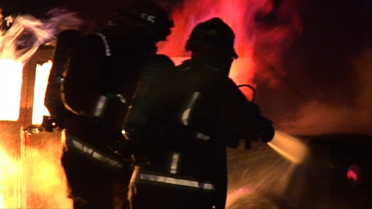 Firefighters using props to hone their firefighting skills at night