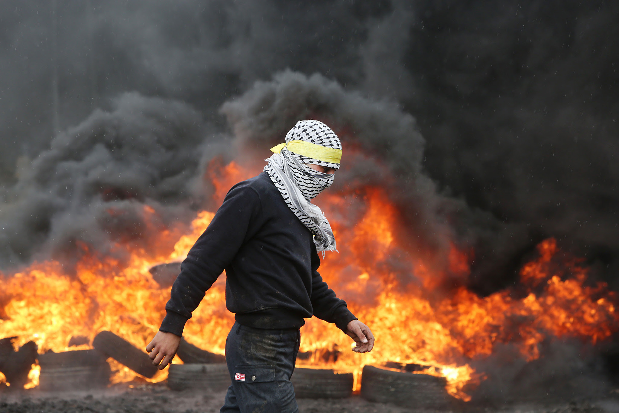 A Palestinian protester walks past burni...A Palestinian protester walks past burning tyres during clashes with Israeli security forces following a demonstration against the expropriation of Palestinian land by Israel, on January 8, 2016, in the village of Kafr Qaddum, near the city of Nablus in the Israeli occupied West Bank. AFP PHOTO / JAAFAR ASHTIYEHJAAFAR ASHTIYEH/AFP/Getty Images