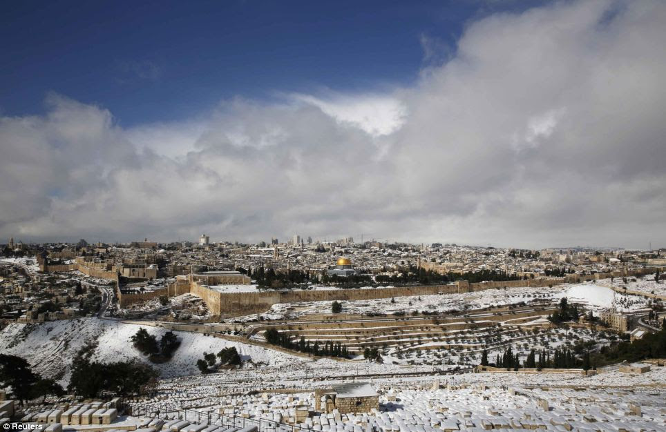 Festive: Jerusalem's Old City following a snowstorm, seen from the Mount of Olives, today