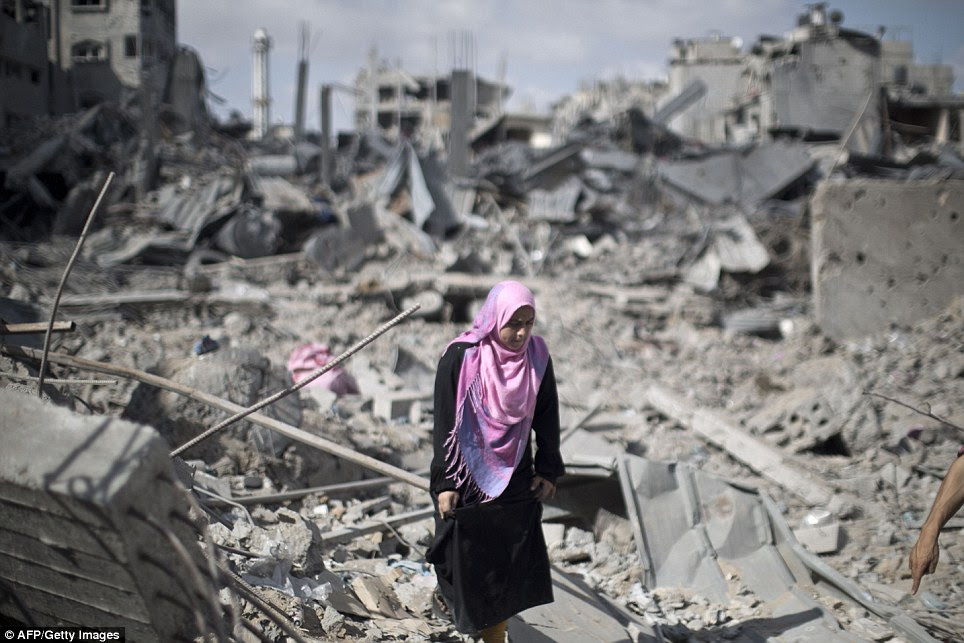 Picking up the pieces: A Palestinian woman walks across the rubble of destroyed buildings in Gaza City as residents returned to examine damage in a 12-hour ceasefire