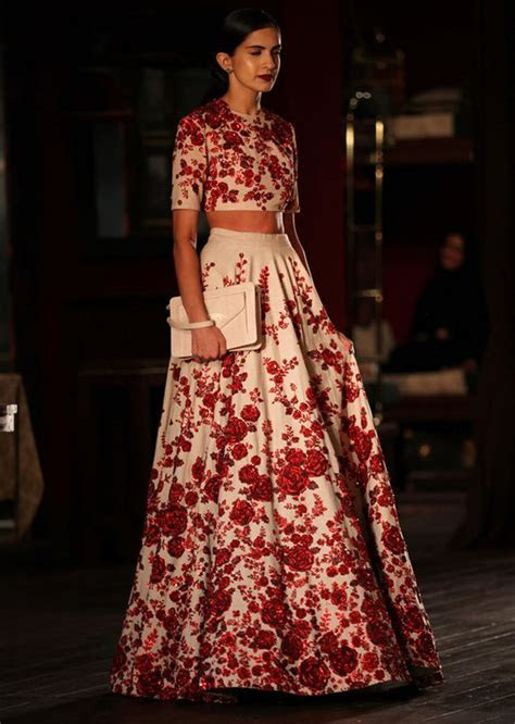Model walking the ramp with red and white floral gown for