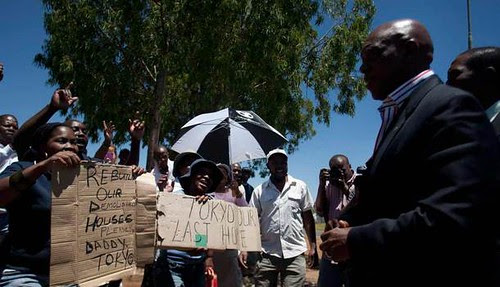 Republic of South Africa Human Settlements Minister Tokyo Sexwale speaking with residents of the informal area around Lenasia. Sexwale was seeking a solution to the crisis after demolition. by Pan-African News Wire File Photos