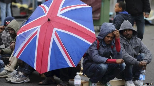 Eritrean migrants take cover from the rain under an umbrella during the daily food distribution at the harbour in Calais